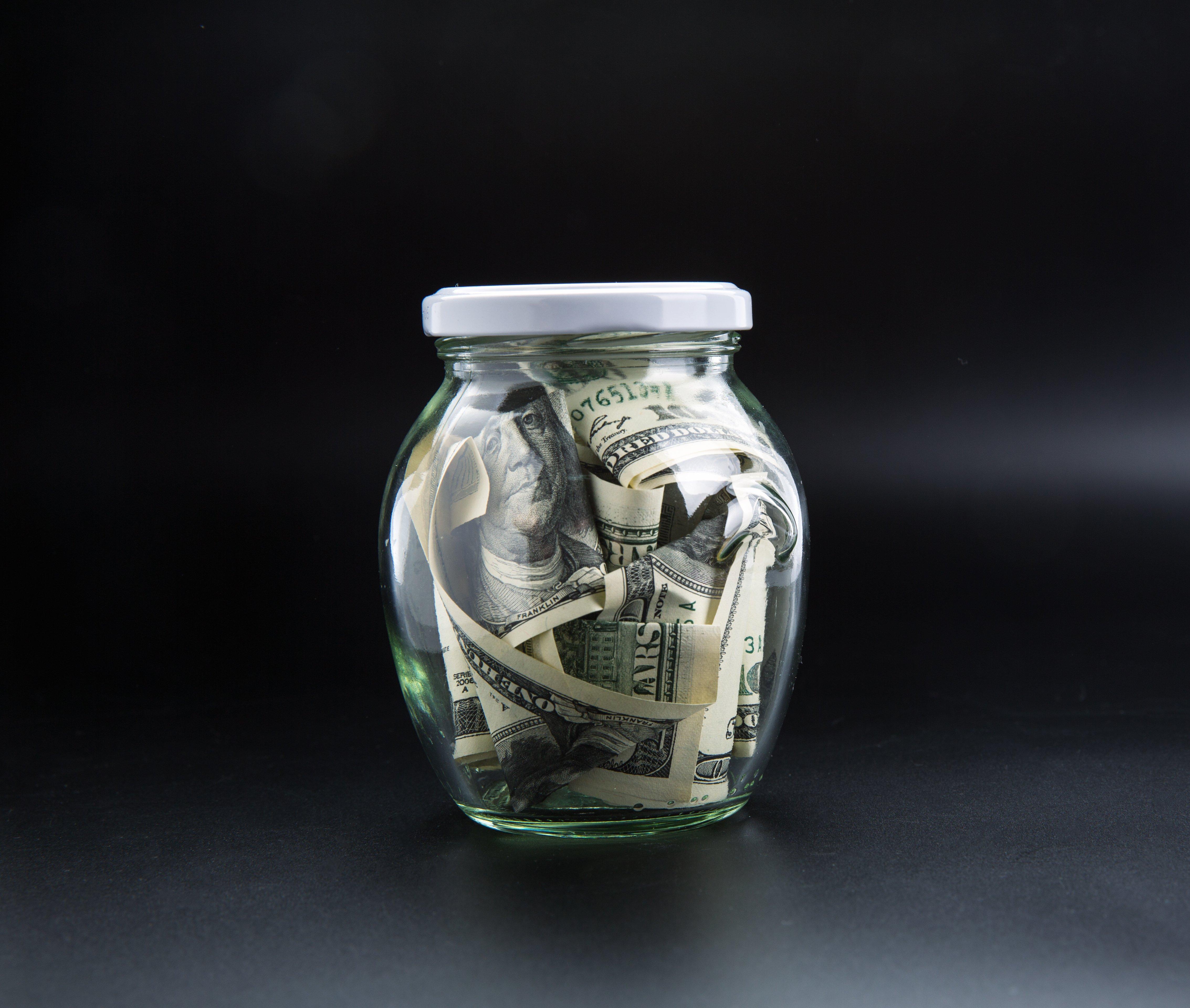 money-saving-concept-glass-jar-full-of-dollars-PWNZMK5